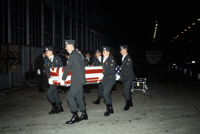 Members of the 101st Airborne Division Honor Guard carry a casket containing the remains of a member of the 3rd Battalion, 502nd Infantry, 101st Airborne Division, out of a temporary morgue. On December 12, 1985, 248 soldiers of the 3rd Battaliion were killed in a plane crash at Gander Airport. They were returning to the United States after participating in peacekeeping duty with the Multi-national Force and Observers in the Sinai Desert