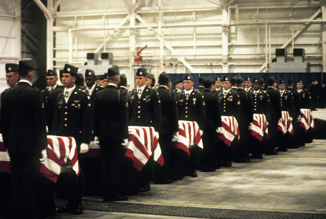 Members of the 101st Airborne Division Honor Guard stand at attention next to caskets containing the remains of a member of the 3rd Bn., 502nd Inf., 101st Airborne Div., during a memorial ceremony. On December 12, 1985, 248 soldiers of the 3rd Battalion were killed in plane crash at Gander Airport, Newfoundland. They were returning to the United States after participating in peacekeeping duty with the Multi-national Force and Observers in the Sinai Desert