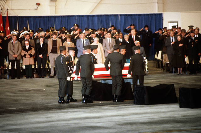 Mourners look on as members of the 101st Airborne Division Honor Guard place a casket containing the remains of a member of the 3rd Bn., 502nd Inf., 101st Airborne Div., onto a bier for a memorial ceremony. On December 12, 1985, 248 soldiers of the 3rd Battalion were killed in plane crash at Gander Airport, Newfoundland, Canada, They were returning to the United States after participating in peacekeeping duty with the Multi-national Force and Observers in the Sinai Desert