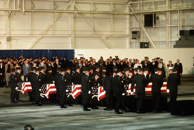 Mourners looks on as members of the 101st Airborne Division carry a casket containing the remains of members of the 3rd Bn., 502nd Inf., 101st Airborne Div., into a hangar for a memorial service. On December 12, 1985, 248 soldiers of the 3rd Battalion were killed in a plane crash at the Gander Airport, Newfoundland, Canada. They were returning to the United States after participating in peacekeeping duty with the Multi-national Force and Observers in the Sinai Desert