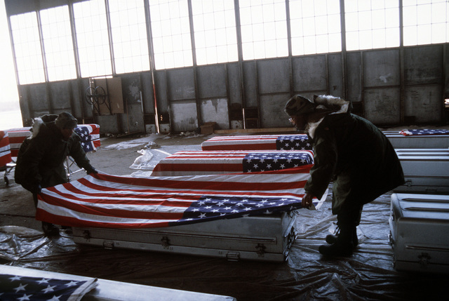 Two soldiers place a flag over a casket containing the remains of a member of the 3rd Bn., 502nd Inf., 101st Airborne Div., while working in a temporary morgue at Gander Airport. On December 12, 1985, 248 soldiers of the 3rd Battalion were killed in a plane crash at the airport. They were returning to the United States after participating in peacekeeping duty with the Multi-national Force and Observers in the Sinai Desert