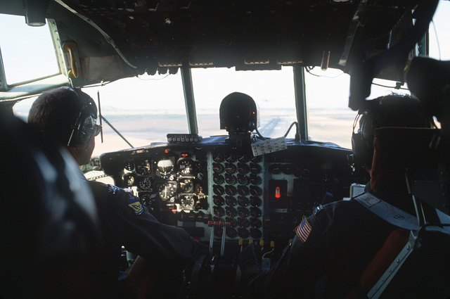 The pilot and copilot of a 21st Tactical Airlift Squadron, 374th Tactical Airlift Wing, C-130E Hercules aircraft wait for permission to take off during an airdrop exercise