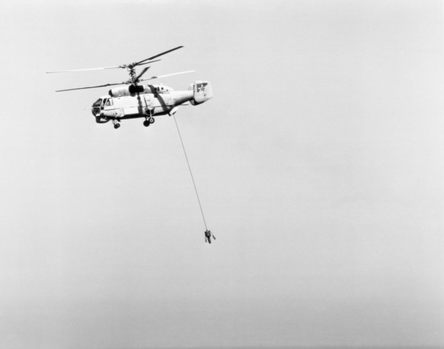 A left side view of a Soviet Ka-27 Helix A anti-submarine warfare helicopter in flight with its dipping sonar deployed