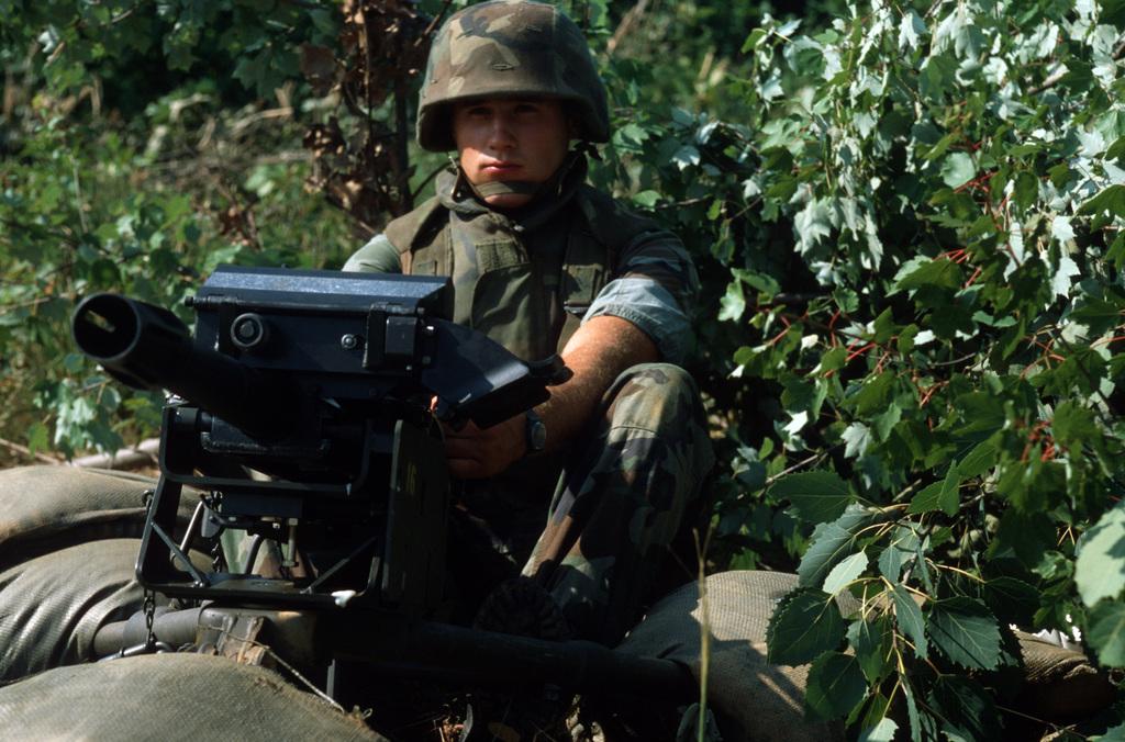 A Marine demonstrates a Mark 19 Mod 3 40 mm machine gun.  The gun fires high velocity belted grenade ammunition