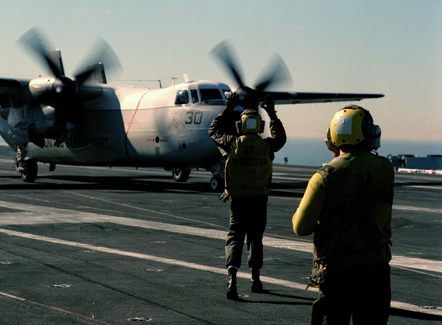 A plane director signals to a C-2A Greyhound aircraft during flight operations aboard the nuclear-powered aircraft carrier USS CARL VINSON (CVN 70)