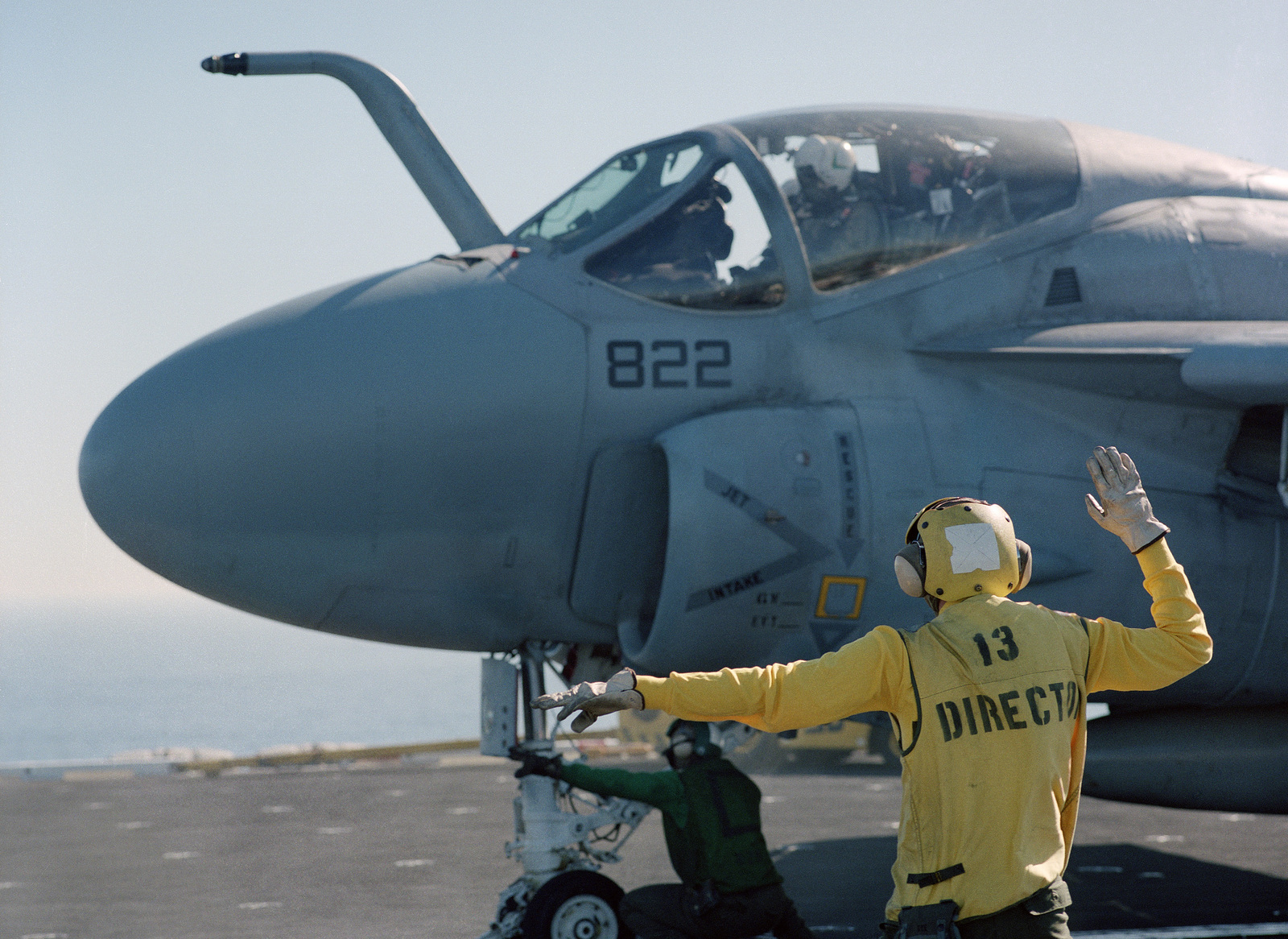 A plane director signals to an A-6E Intruder aircraft on a catapult during flight operations aboard the nuclear-powered aircraft carrier USS CARL VINSON (CVN-70)