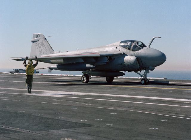 A plane director signals to an A-6E Intruder aircraft that has just landed during flight operations aboard the nuclear-powered aircraft carrier USS CARL VINSON (CVN-70)