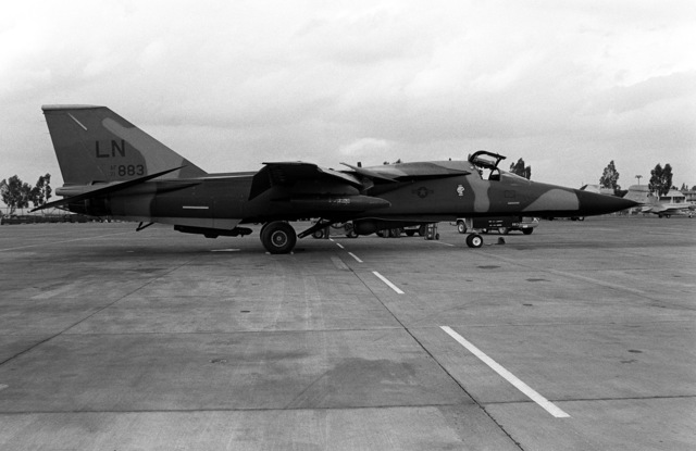 A right side view of a U.S. Air Force F-111 aircraft parked on the flight line. The aircraft is assigned to the 48th Tactical Fighter Wing, which is based in England