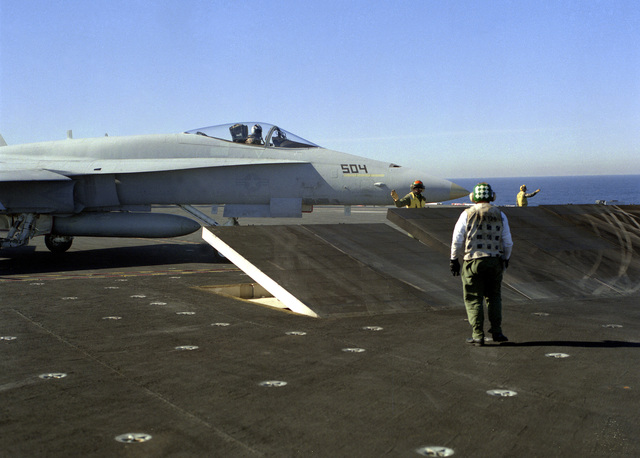 A squadron plane inspector watches as an F/A-18A Hornet aircraft of Strike Fighter Squadron 125 taxis behind a partially raised jet blast deflector during flight operations aboard the nuclear-powered aircraft carrier USS CARL VINSON (CVN-70)