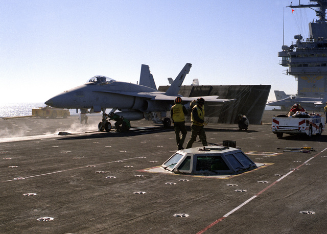 A squadron plane inspector watches as an F/A-18A Hornet aircraft of Strike Fighter Squadron 125 is positioned on a catapult during flight operations aboard the nuclear-powered aircraft carrier USS CARL VINSON (CVN-70). Behind the aircraft is a raised jet blast deflector and in the foreground is the control room for the integrated catapult control system
