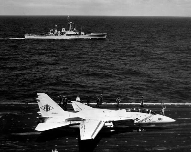 A starboard beam view of the British Leander class frigate HMS APOLLO (F 70) underway as seen from the bridge of the aircraft carrier USS AMERICA (CV 66) during Fleet Exercise 1-86. An F-14A Tomcat aircraft from Fighter Squadron 102 is about to be launched from a catapult in the foreground. The aircraft is armed with an AIM-54 Phoenix missile