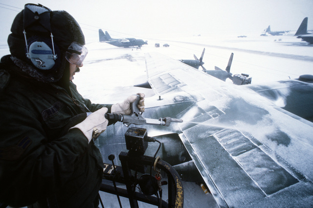 A USAF ground crewman deices the wing of a C-130 Hercules cargo aircraft on a snow covered Rhein Main Air Base, Germany flight line ramp. Exact Date Shot Unknown
