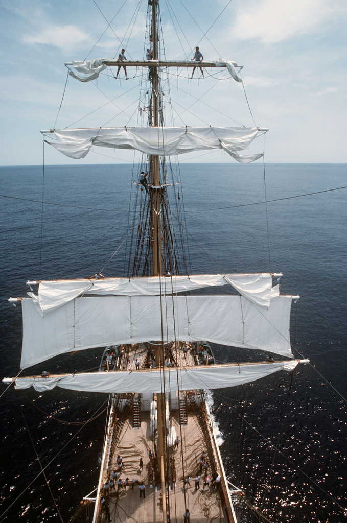 A view, as seen from the mizzen mast, of Coast Guard cadets reefing the main sky sail of the US Coast Guard training bark USCGC EAGLE (WIX 327) during a training cruise
