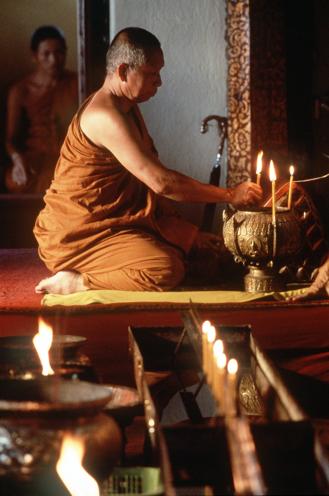 Bhuddist monk places candle at alter in Bangkok temple. Exact Date Shot Unknown