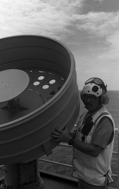 CHIEF Radioman Rick Davis performs a routine check on a satellite communications antenna aboard the amphibious assault ship USS TARAWA (LHA 1) during Exercise COBRA GOLD '86