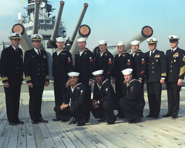 Crew members chosen for petty officer or non-rated man of the month in 1985 pose for a photo aboard the battleship USS IOWA (BB 61). Kneeling left to right: YN3 (SW) Marc Carlock, YN3 Jerry Mayes and LT3 Dru Rhyne. Standing left to right: Commander (CDR) A.C. Beck Jr., executive officer; Captain (CAPT) Gerald E. Gneckow, commanding officer; PN2 Robert Lemmond, YN2 (SW) Rick Rowe, MA1 (SW) John Zelnik, YN1 (SW) Dave Chambers, PH1 (SW) Jeff Hilton, Lieutenant Commander (LCDR) O.W. Wright and BMCM (SW) Bobby Scott, command master chief