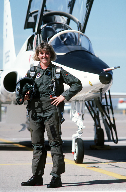 First Lieutenant (1LT) Kara Hayes, T-38 instructor pilot, stands in front of her aircraft