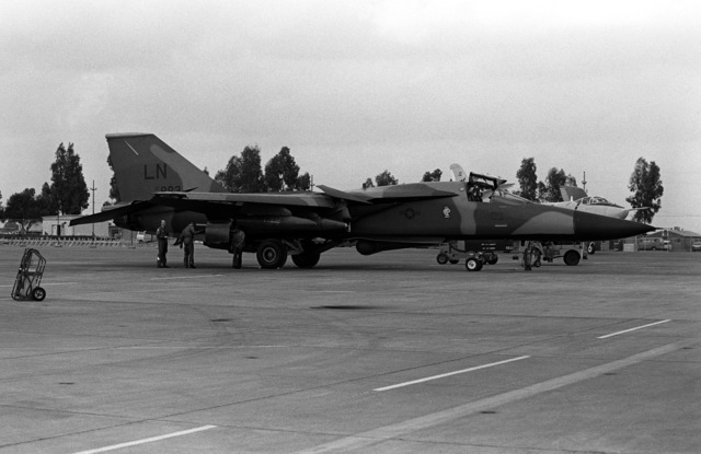 The crew of a U.S. Air Force F-111 aircraft conducts a check of their aircraft on the flight line. The aircraft is assigned to the 48th Tactical Fighter Wing, which is based in England