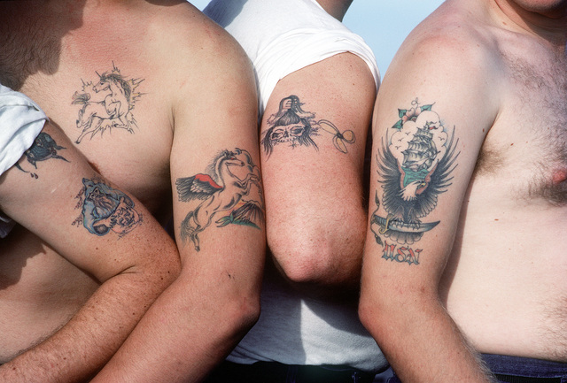 The tattooed arms of a group of sailors