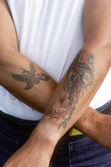 The tattooed arms of a sailor