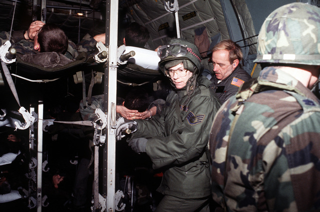 U.S. Army medical personnel and C-130 Hercules aircraft crew members prepare simulated casualties for airlift to RAF Mildenhall, England, during Certain Sentinel, a part of exercise Reforger '86