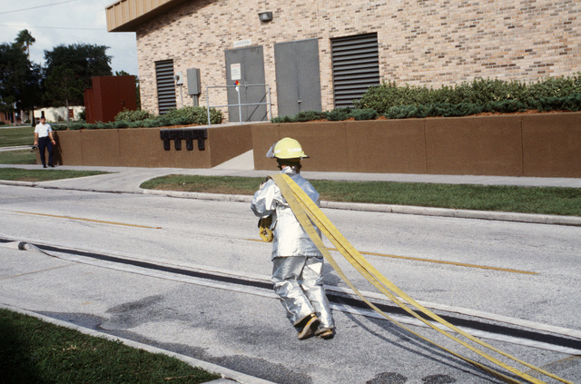 AIRMAN First Class (A1C) Rachel E. Hedge, a fire protection specialist assigned to the 56th Civil Engineering Squadron carries a water hose to a fire hose to a fire hydrant during a training exercise. She is wearing a proximity suit