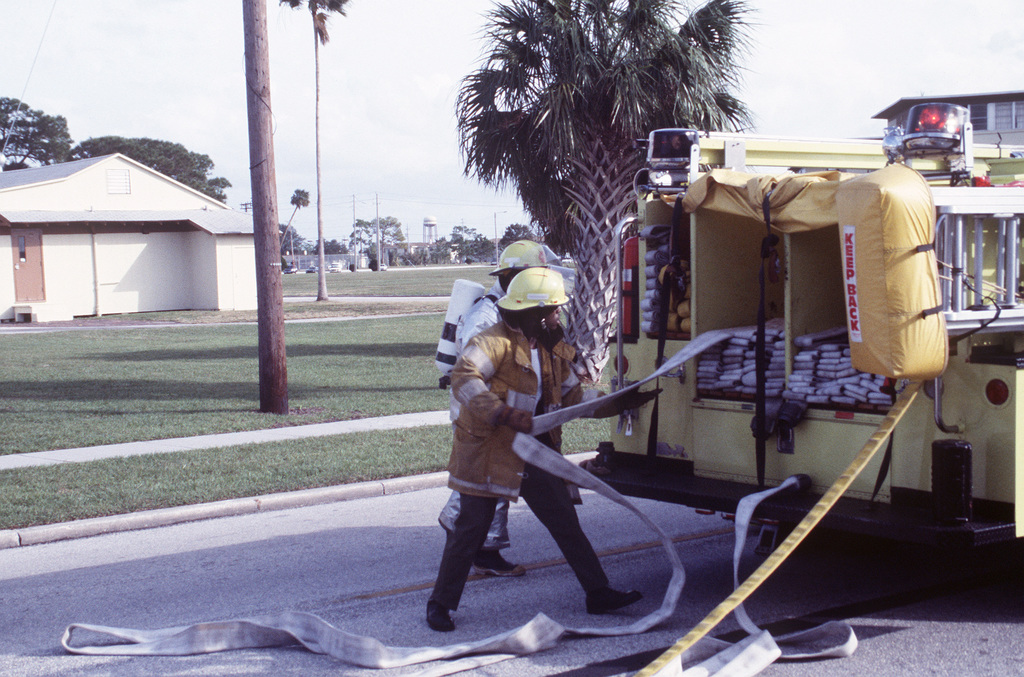 Two US Air Force fire protection specialists assigned to the 56th Civil Engineering Squadron remove water hoses from a fire engine during a training exercise