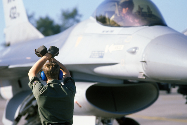 A crew chief signals instructions to the pilot of an F-16 Fighting Falcon aircraft on the flight line during Exercise COPE THUNDER '86-3. During the exercise more than 60 aircraft from the US and the Far East will be pitted against each other in daily combat scenarios, dogfights and bomb runs