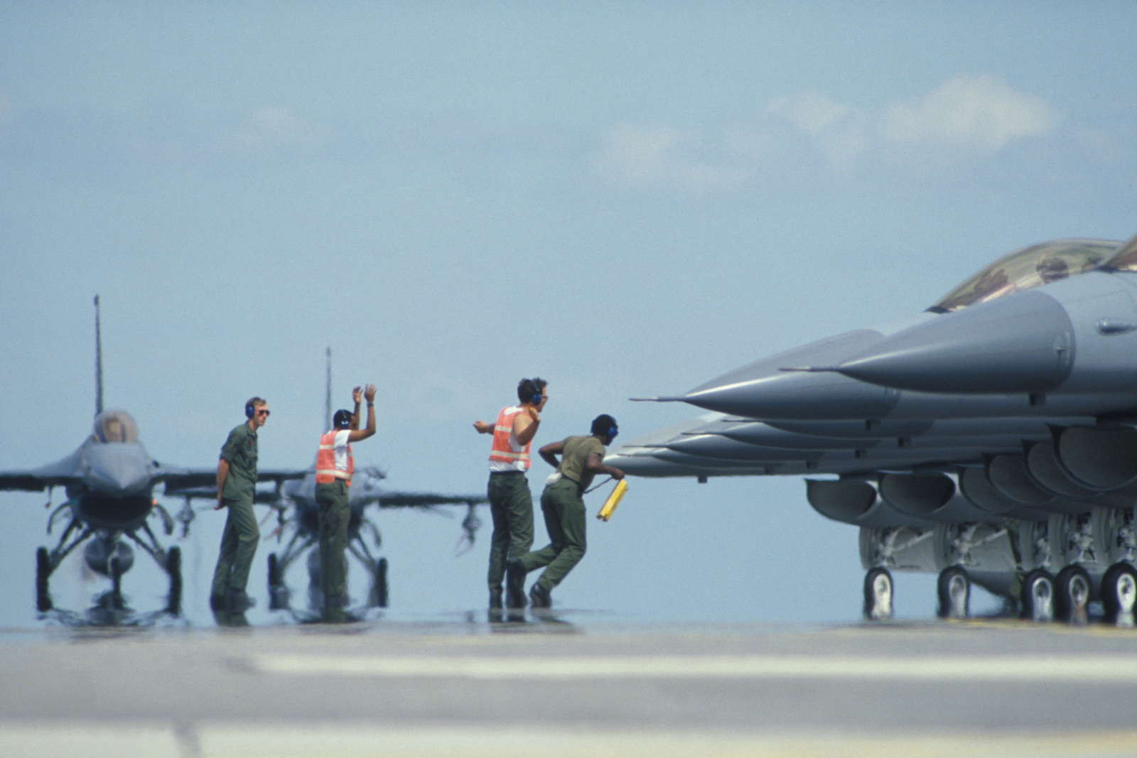 Members of the ground crew prepare a squadron of F-16