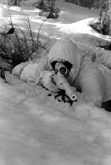 CPL. Scott C. Anderson, Scout Sniper Platoon, 23rd Marines, 5th Mar. Div., takes aim on a target with a sniper rifle during a cold weather training exercise