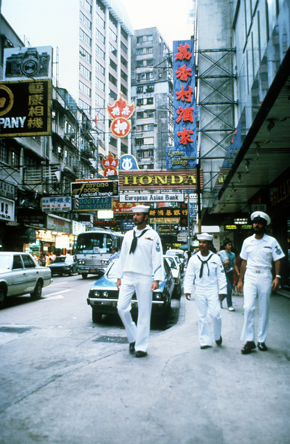 Torpedoman's Mate 1ST Class Terry Morse, GUNNER's Mate 2nd Class Lloyd Basilio and Interior Communications Electrician 1ST Class Larry Petrongelli (left to right) stroll the streets during liberty from their Seventh Fleet frigates anchored in Hong Kong harbor