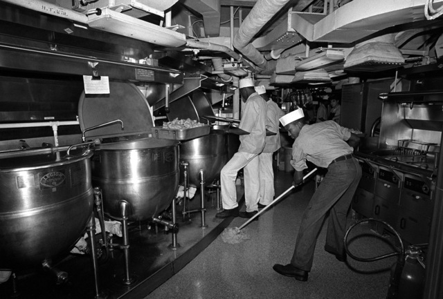 Mess Spcialists work around a semicircle of cooking kettles in the main enlisted galley aboard the battleship USS IOWA (BB-61)