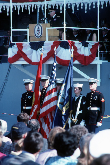 A color guard stands at attention beneath the speakers platform as Brigadier General (BGEN) William C. Page, director, Operations, Plans and Mobilization, US Armed Forces Command, speaks during the commissioning of the guided missile cruiser USS VALLEY FORGE (CG 50)