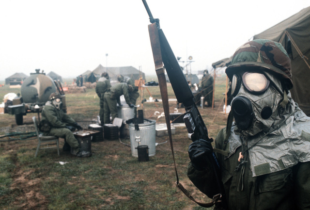 A member of the 1606th Services Squadron, wearing chemical warfare gear and armed with an M-16 rifle, stands guard at the field dining facility during the mission capability inspection PURPLE DUCK '86-12
