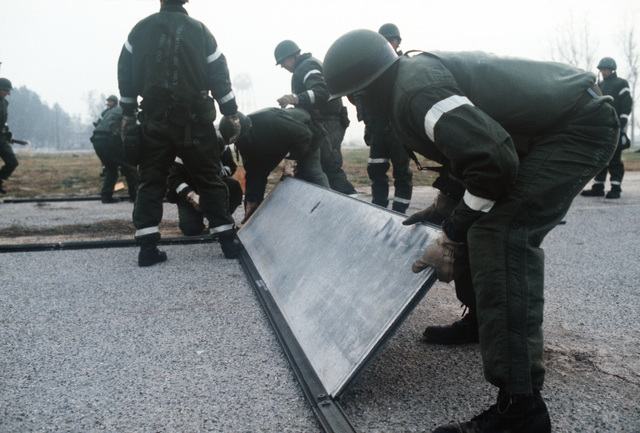 Members of the 1606th Civil Engineering Squadron align steel plates during a rapid runway repair operation. The exercise is part of the mission capability inspection PURPLE DUCK '86-12