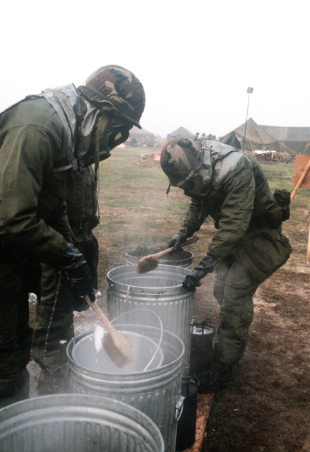 Members of the 1606th Services Squadron wear chemical warfare gear while washing dishes in the field dining facility during the mission capability inspection PURPLE DUCK '86-12