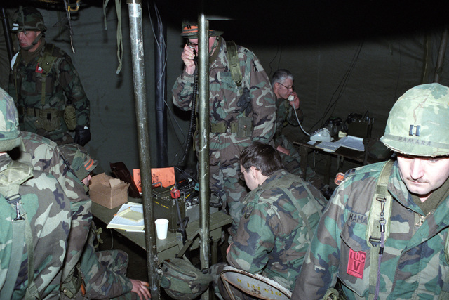An officer sends a message on a field radio in the tactical operations center of the 32nd Separate Infantry Brigade (Mechanized), Wisconsin Army National Guard, during Exercise REFORGER '86