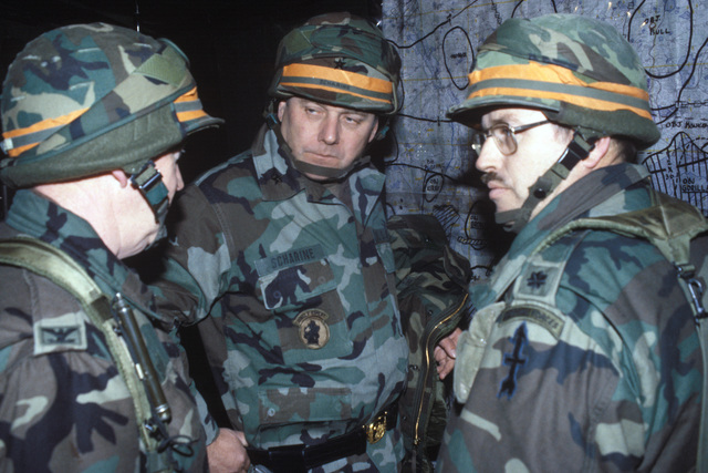 Brigadier General (BGEN) Charles Scharine, center, commander of the 32nd Separate Infantry Brigade (Mechanized), Wisconsin Army National Guard, confers with his staff officers in the tactical operations center during Exercise REFORGER '86