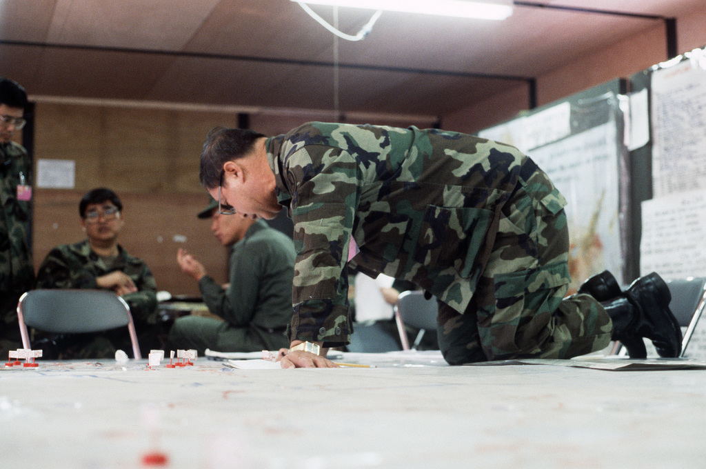 A member of IX Corps, US Army Reserve, arranges markers on a situation map during Exercise YAMA SAKURA IX at Camp Chitose