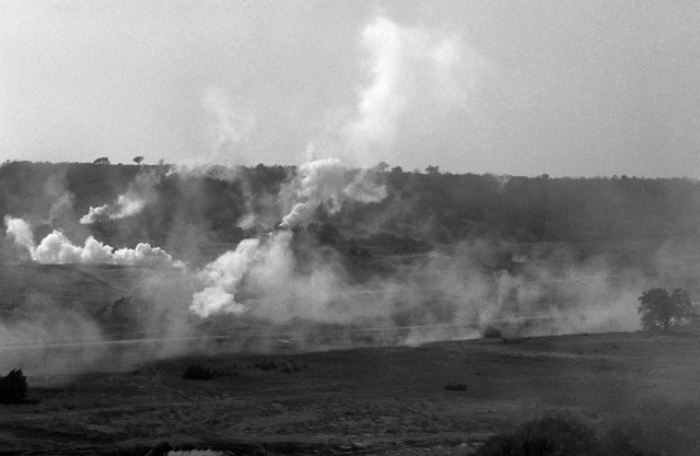 Smoke and dust obscure the battlefield as camouflaged M-2 Bradley infantry fighting vehicles support the final assault by members of the 2nd Bn., 41st Inf., 2nd Armored Div., during a company team attack exercise at the Shell Point training area