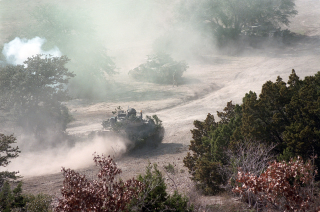 Smoke and dust obscure the battlefield as camouflaged M2 Bradley infantry fighting vehicles support the final assault by members of Infantrymen of the 2nd Battalion, 41st Infantry, 2nd Armored Division, during a company team attack exercise at the Shell Point training area