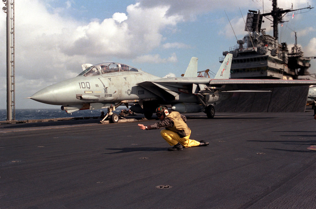 A catapult officer aboard the aircraft carrier USS SARATOGA (CV 60) signals with two fingers that everything is ready and an F-14A Tomcat aircraft is ready to be launched. The aircraft is armed with AIM-7 Sparrow missiles on the fuselage and AIM-9 Sidewinder on the wing pylons