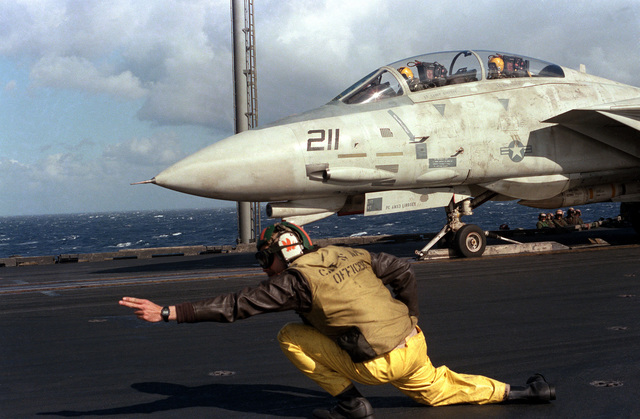 A catapult officer aboard the aircraft carrier USS SARATOGA (CV 60) signals with two fingers that an F-14A Tomcat aircraft is ready to be launched. The aircraft is armed with AIM-54A Phoenix missile on the fuselage station