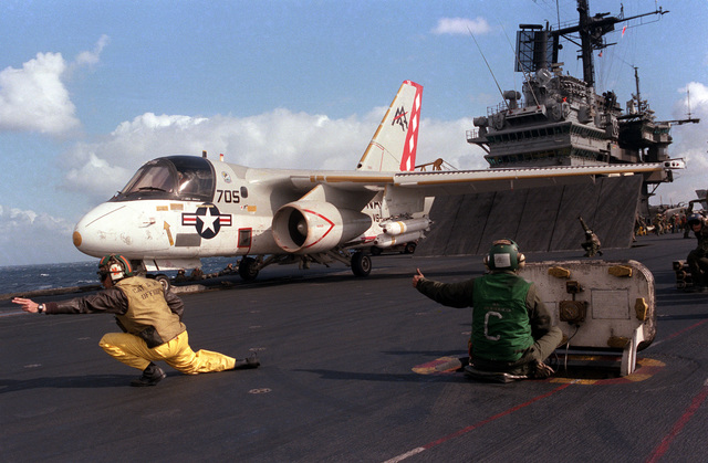 A catapult officer aboard the aircraft carrier USS SARATOGA (CV 60) signals with two fingers that an S-3A Viking aircraft is ready to be launched. The aircraft is armed with two Mark 20 Rockeye II cluster bombs on the left wing pylon