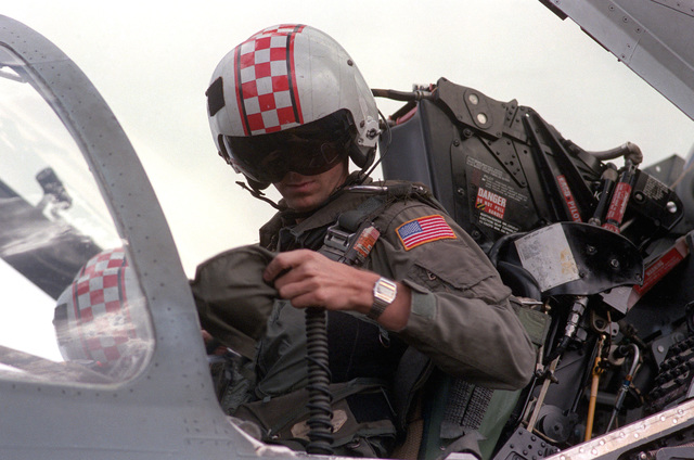 A pilot straps himself in the cockpit of his aircraft prior to a mission during flight operations aboard the aircraft carrier USS SARATOGA (CV 60)