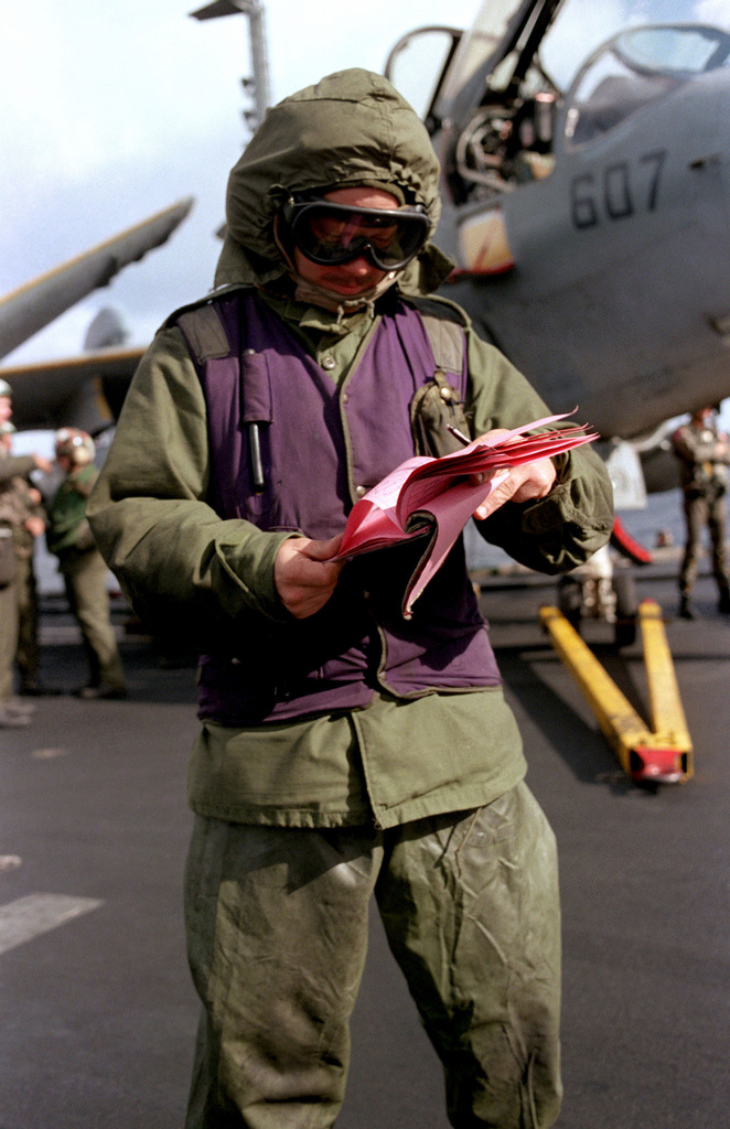 An aviation fuelman looks over his paperwork prior to the start of flight operations aboard the aircraft carrier USS SARATOGA (CV 60)