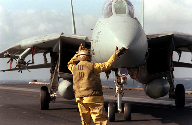 An F-14A Tomcat aircraft is directed to a catapult during flight operations aboard the aircraft carrier USS SARATOGA (CV 60)