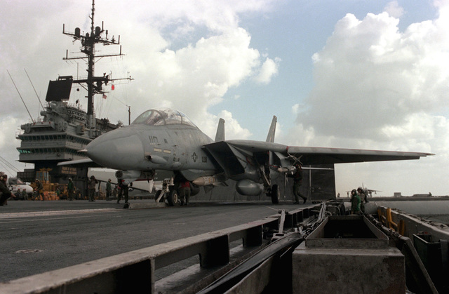 An F-14A Tomcat aircraft is inspected while on a catapult prior to launch from the aircraft carrier USS SARATOGA (CV 60). The aircraft is armed with AIM-54 Phoenix missile on the fuselage station and an AIM-7 Sparrow and AIM-9 Sidewinder on the left wing