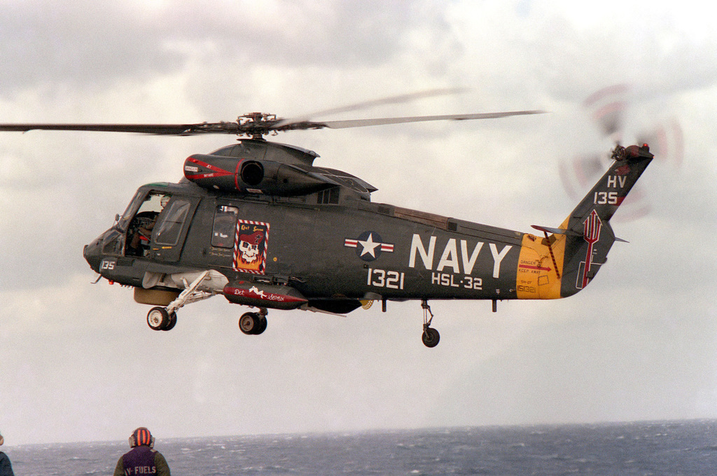 An SH-2F helicopter from Helicopter Light Anti-Submarine Squadron 34 hovers above the aircraft carrier USS SARATOGA (CV 60) during flight operations