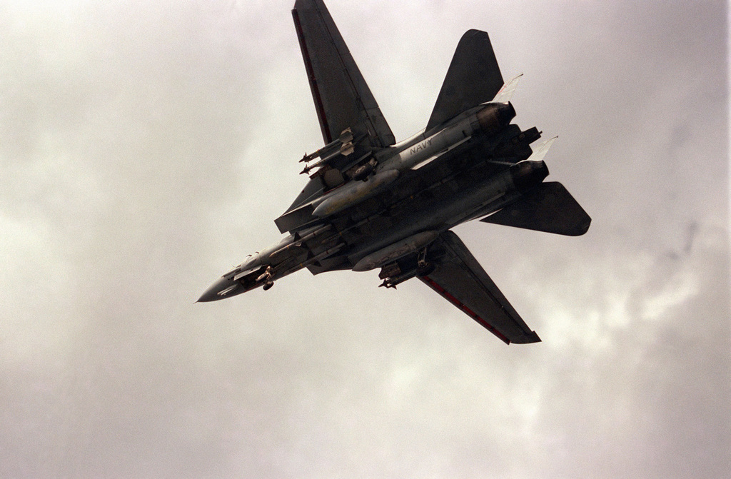 An underside view of an F-14A Tomcat aircraft in flight over the aircraft carrier USS SARATOGA (CV 60). The aircraft is armed with AIM-7 Sparrow missiles on the fuselage stations and AIM-9 Sidewinder missiles on the wing pylons